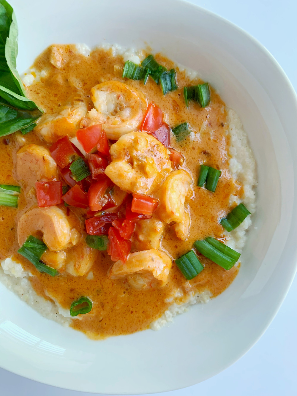 overhead shot of cajun shrimp and grits with tomato sauce, a basil leaf, and green onions