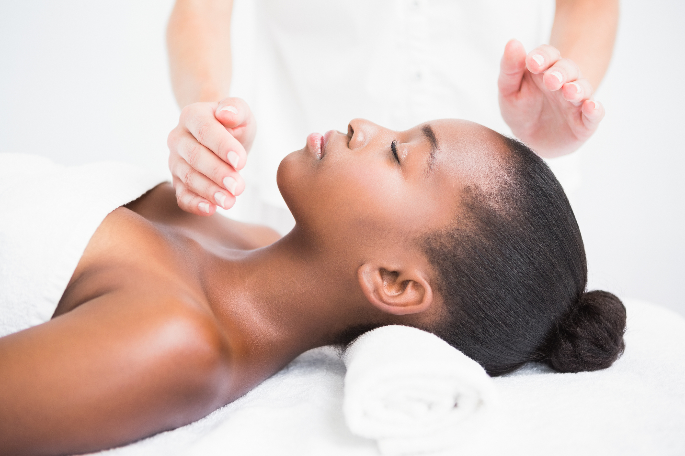 Pretty woman enjoying a reiki technique at the health spa.jpg