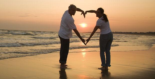 Couple on the beach making heart shape