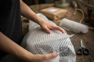 a-woman-wrapping-an-item-in-bubble-wrap-
