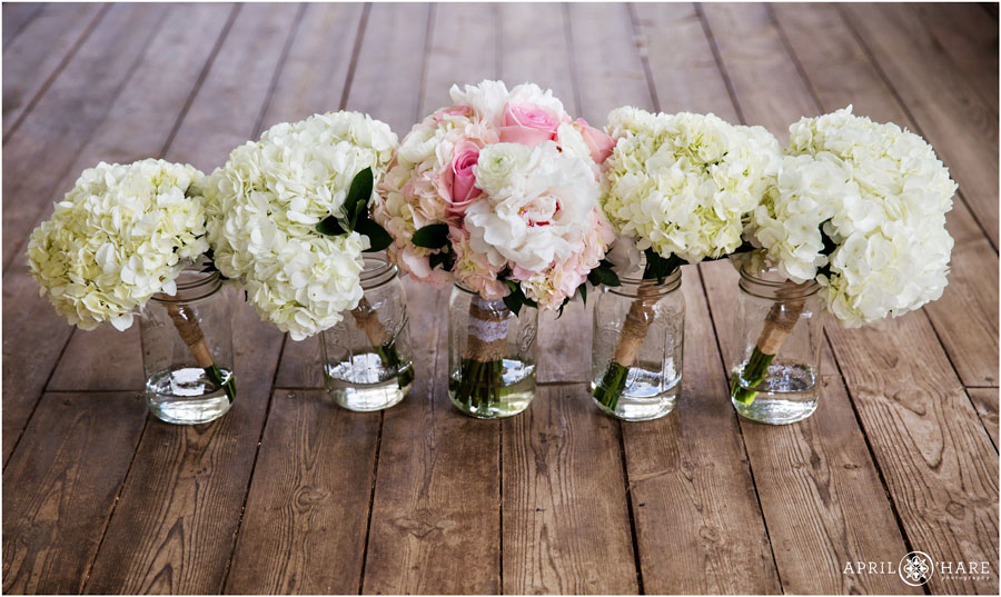 Creamy-white-and-pastel-pink-hydrangea-bouquets-on-a-wood-floor-on-the-patio-at-Denver-Botanic-Garde