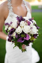 Bride holding bridal bouquet with purple and white flowers