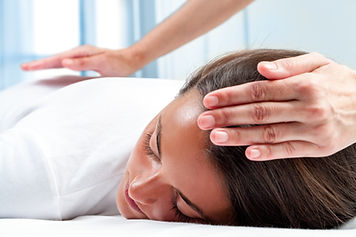 Therapists hands doing reiki therapy on