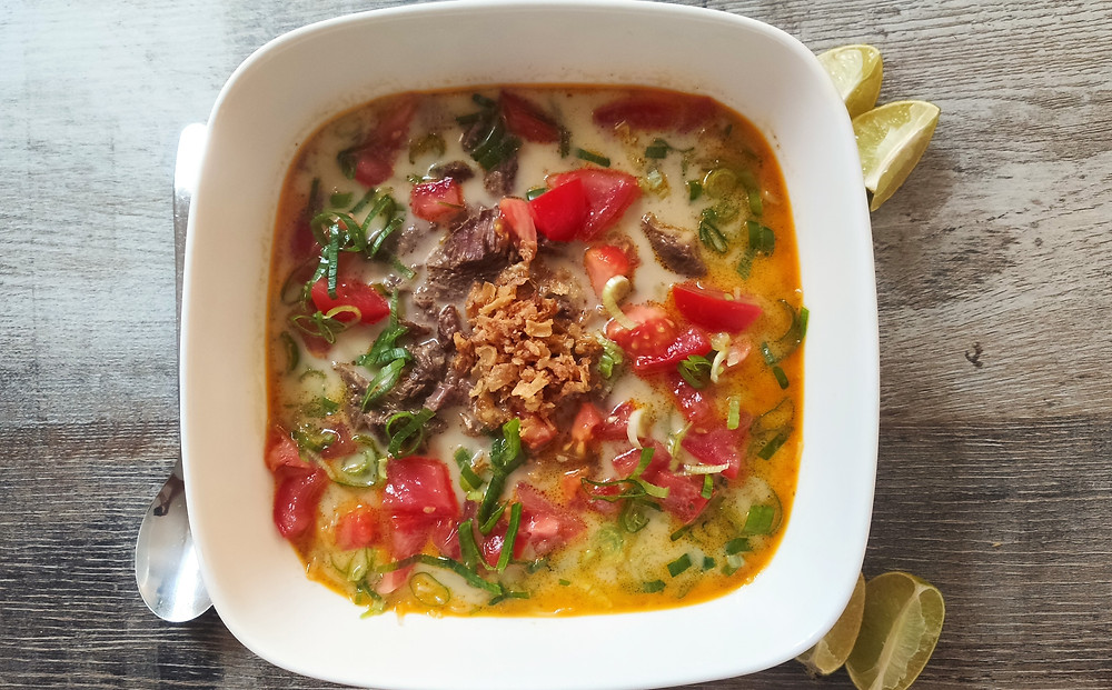 Soto Betawi, Indonesian beef soup from Jakarta with tomatoes, spring onions, coconut and lime wedges in a bowl