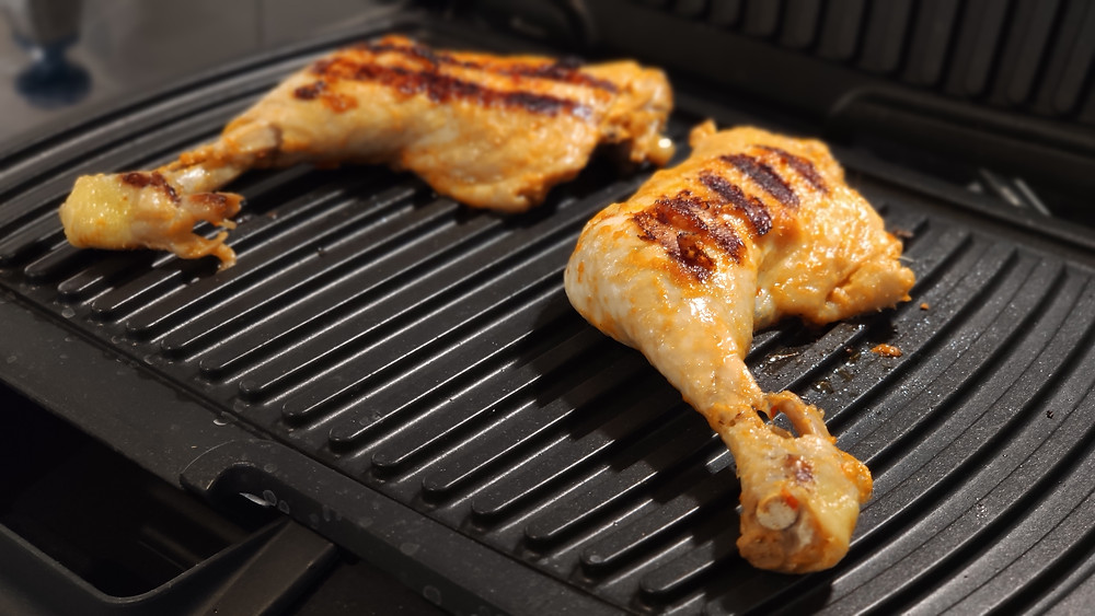 Grilling Ayam Cincane chicken legs on grill
