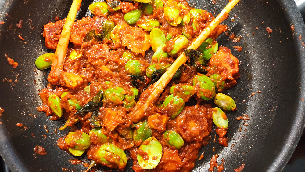 Frying Sambal Goreng Udang Peteh, Indonesian fried chili shrimp with peteh beans, lemongrass and kaffir lime leaves in a pan