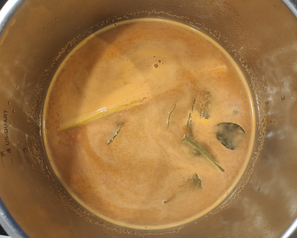 Sayur Asem spice paste with water, lemongrass and salam leaves, boiling in a pan