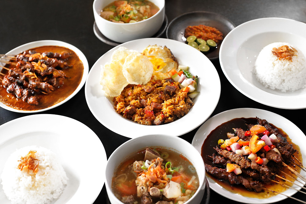 Traditional Indonesian dishes like beef rendang, satay skewers, soto soup, sambal chili paste and rice