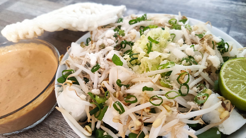 Lotek, Indonesian vegetable salad with a spiced fresh peanut dressing with kencur on a plate on a table