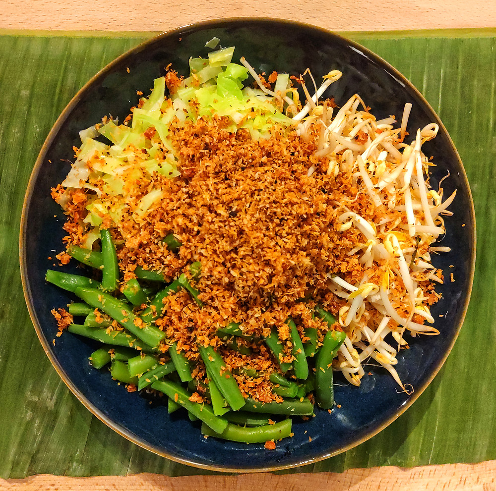 Urap Urap, Indonesian mixed vegetables with a spiced grated coconut topping, on a blue plate on green banana leaf