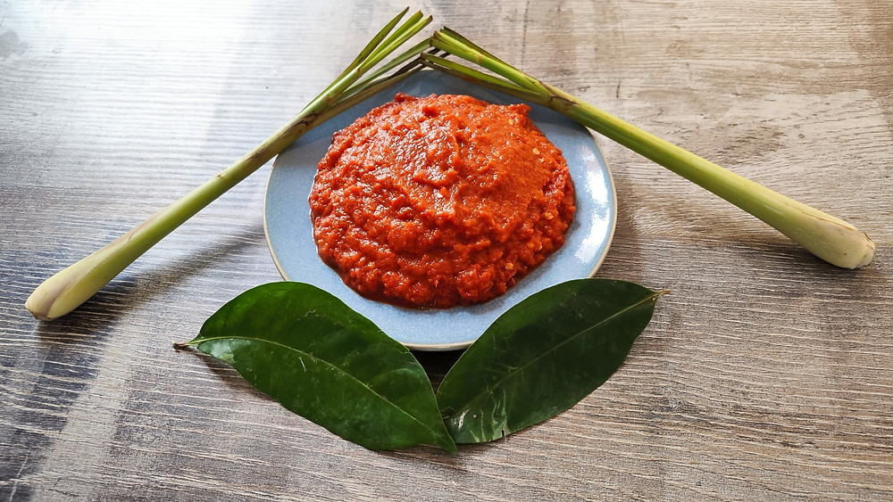 Ayam Cincane spice paste (bumbu) with lemongrass and salam leaves on a plate on a table