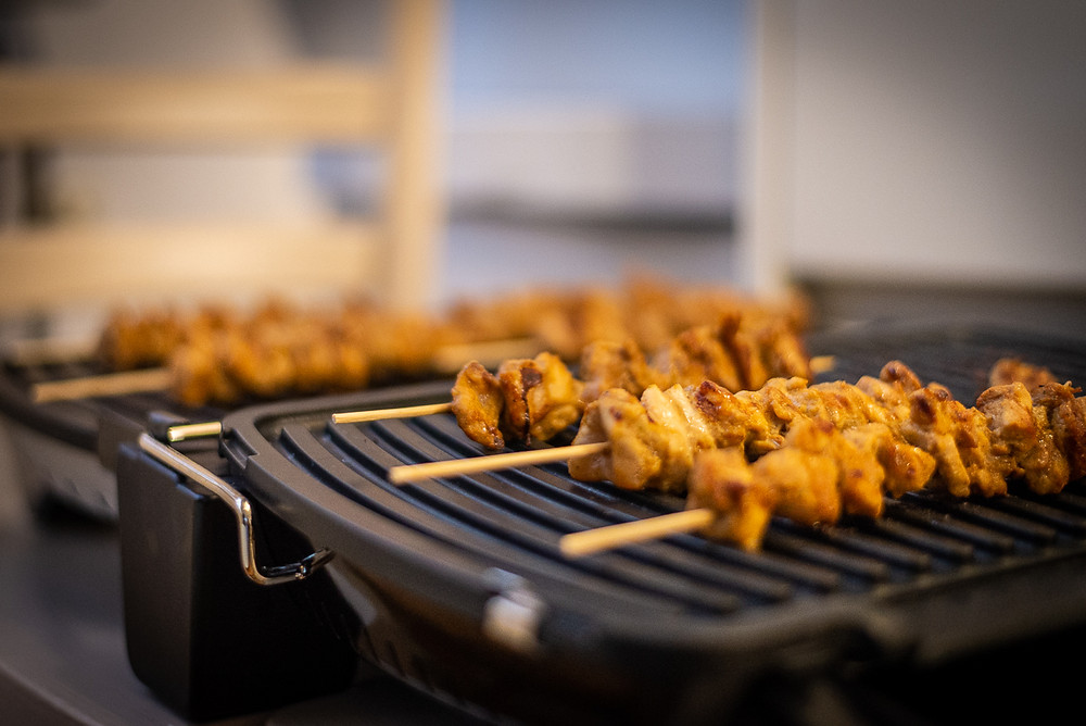 Sate Ayam: Indonesian chicken satay skewers on a grill