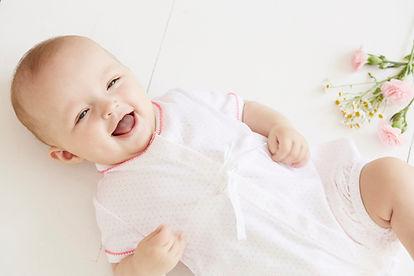 bébé qui rigole au éclat avec fleurs