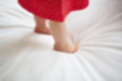 bébé debout dans le lit avec robe rouge a poix