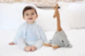 bébé qui sourit avec sa peluche