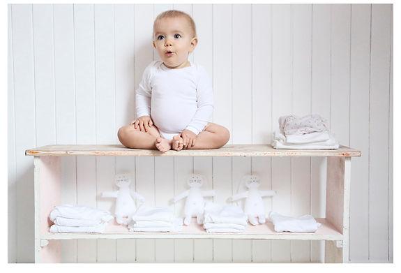 bébé en body blanc sur son banc