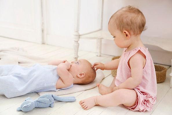 deux bébé au sol en tenu d'été qui jouent