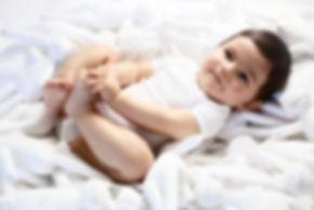 bébé qui dors dans ses peluche en body blanc petit bateau