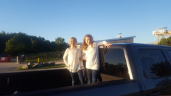 Image of Brady's daughters standing in truck bed