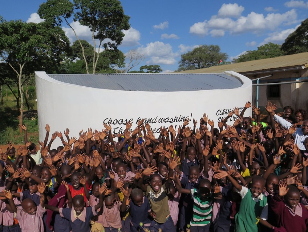 Children next to school water tanks. These enable the children to stay in school so they don't have to trek long distances for water