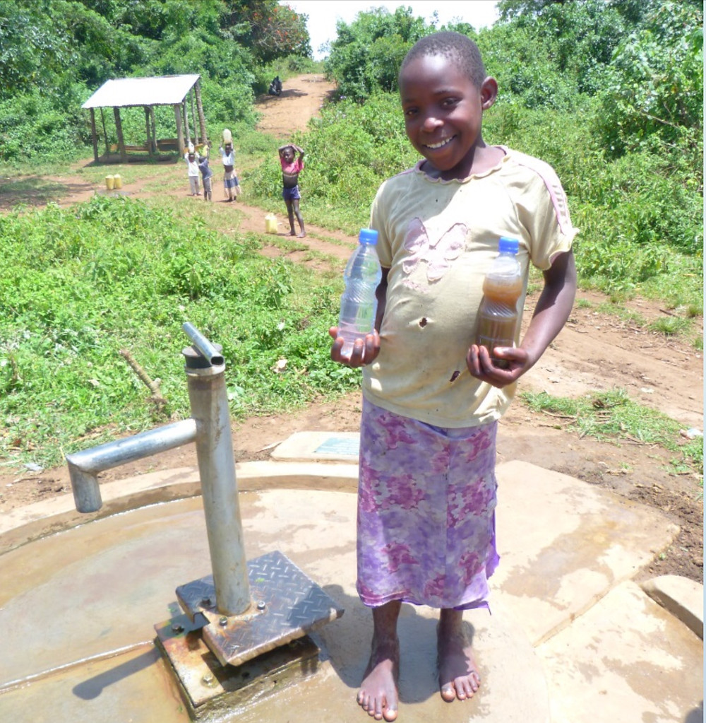 A child showing the water she used to drink and the water she now drinks from the borehole Just A Drop supported