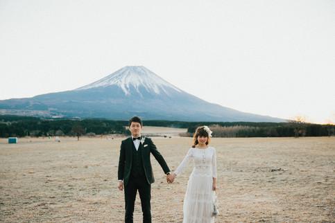 富士山の前で手を繋ぐ男女
