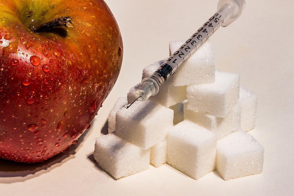 An insulin syringe resting among sugar cubes and an apple