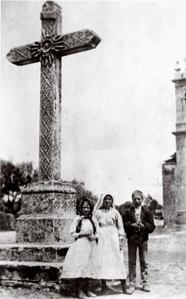The three Fatima children, Lucia, Francisco and Jacinta before the Cross.