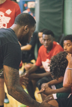 Coach Kendly (Regis College) offering advice to his team