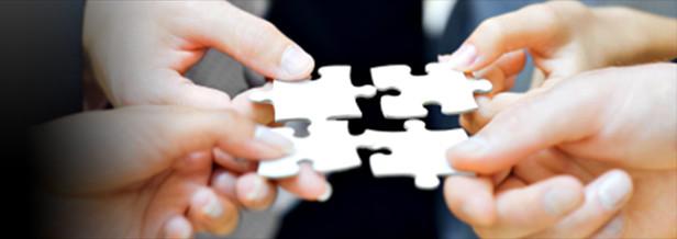 Four hands holding interlocking puzzle pieces