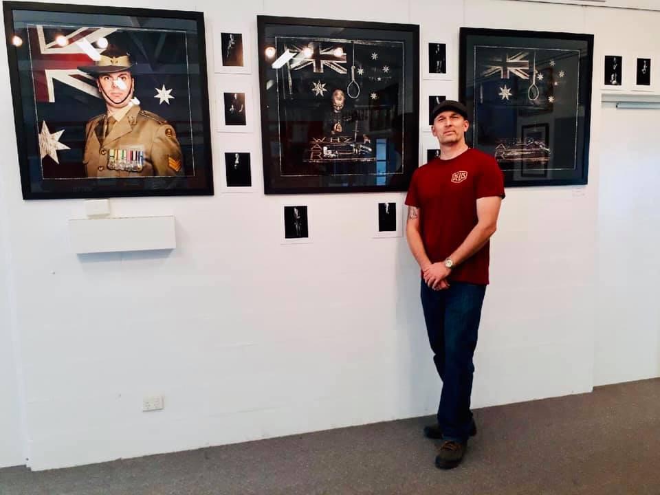Craig and wall of photos.jpg