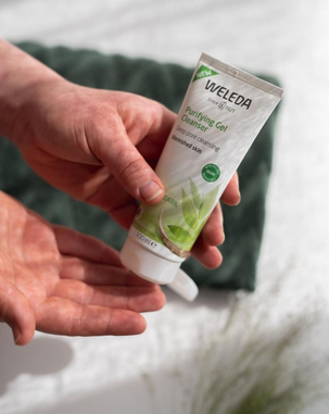 Hands squeezing some Weleda Purifying Gel Cleanser