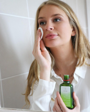 Blonde haired woman cleansing her face with Weleda Aknedoron Cleansing Lotion