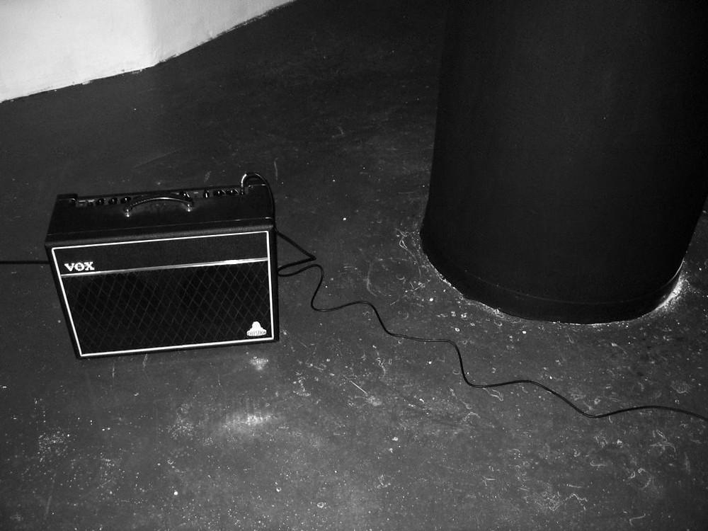 La estructura del silencio. Intervención sonora. (detalle) columnas pintadas de negro, pie, micrófono y amplificador