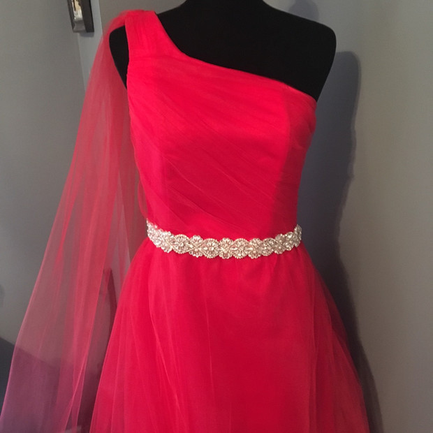 Red custom bridesmaid dress of satin with an overlay of tulle.  The design was completed with a rhinestone belt.