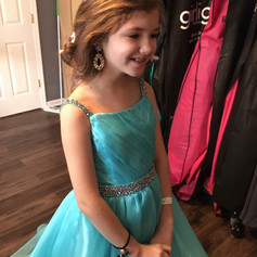 Sweet pageant gown in aqua organza with a ruched bodice. Hand sewn rhinestones complete this at the straps and waistline.