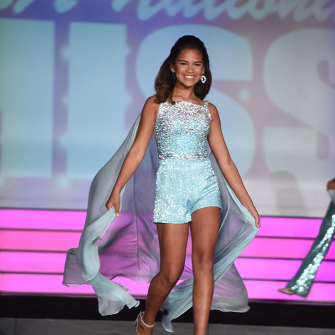 This custom designed fun fashion was covered in over 6500 handsewn faceted Swarovski rhinestones applied in the ombre style going from crystal at the neckline fading into aqua blue at the bottom half. Several thousand bugle beads for the liquid beaded shorts were used.  The cape was made of silk chiffon.