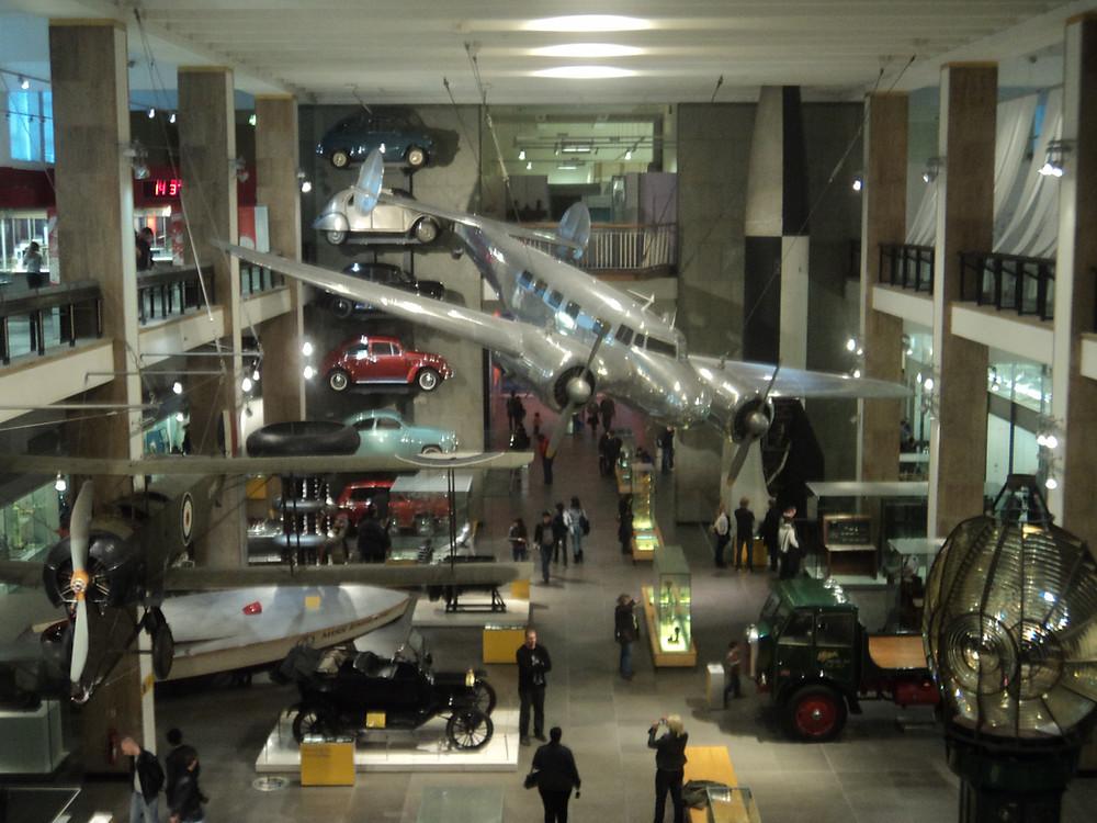 Foto interior Science Museum. Exposição de aviões e carros.