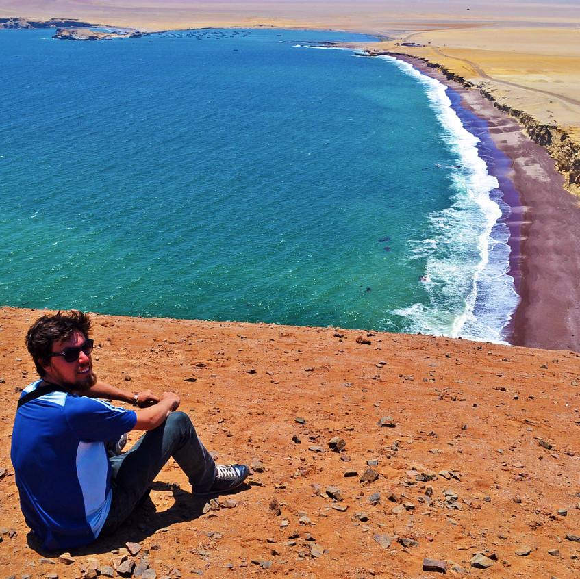 Homem sentado no morro ao lado do lado da Playa Roja - Paracas