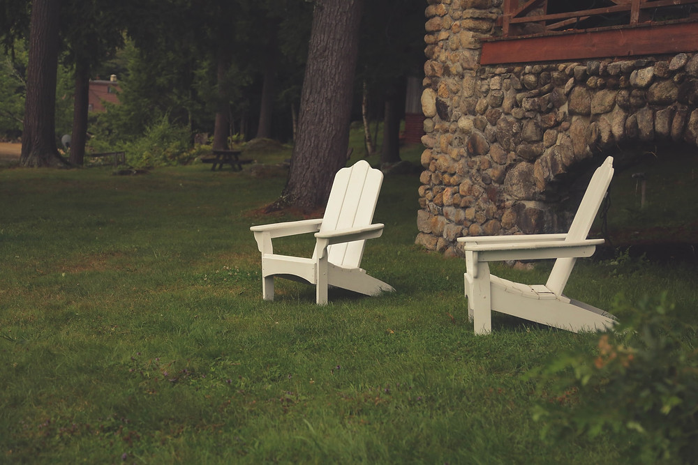two white Adirondack chairs on a lawn near a stone wall and picnic area