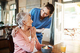 white female nurse smiling at white elderly female eating breakfast