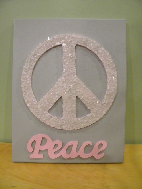 The Background Painted With Gray Paint An Peace Sign In Light Pink Accented Clear Glittered Stone Pieces On It