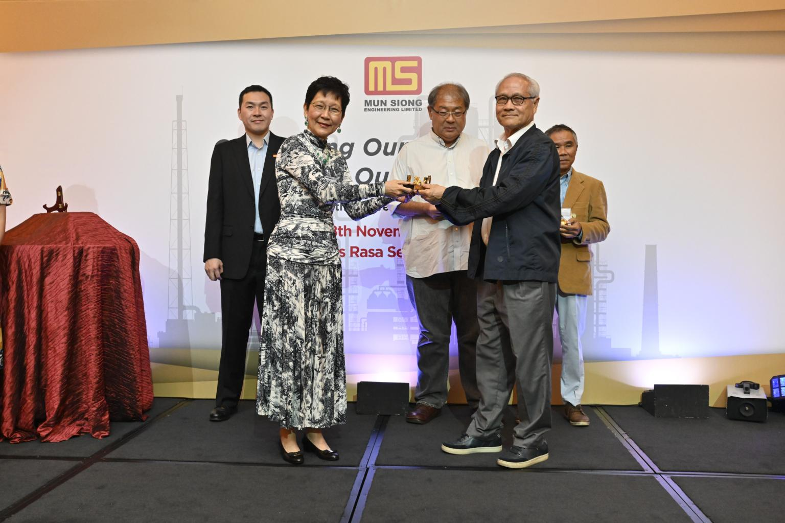 Independent Director, Dr. Lau Teik Soon receiving a token of appreciation from Executive Chairlady of Mun Siong Engineering Limited.