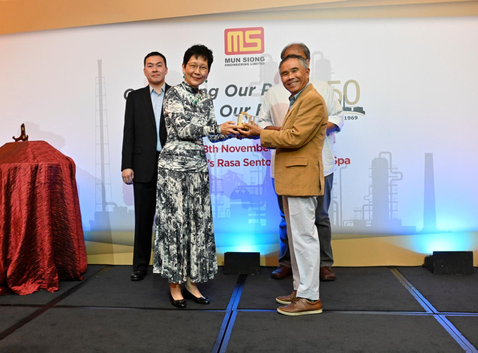 Independent Director, Mr. Sim Swee Yam receiving a token of appreciation from Executive Chairlady of Mun Siong Engineering Limited.