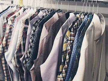 Freshly ironed shirts hung up on a rack.