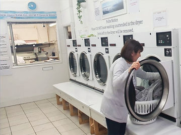 An Ironing R Us staff member loading a duvet into a dryer.