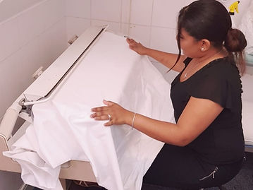 Ironing R Us staff member using a roller to iron bed sheets.
