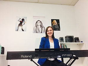 A singing teacher sits in the teaching room in front of her keyboard, ready for a singing lesson