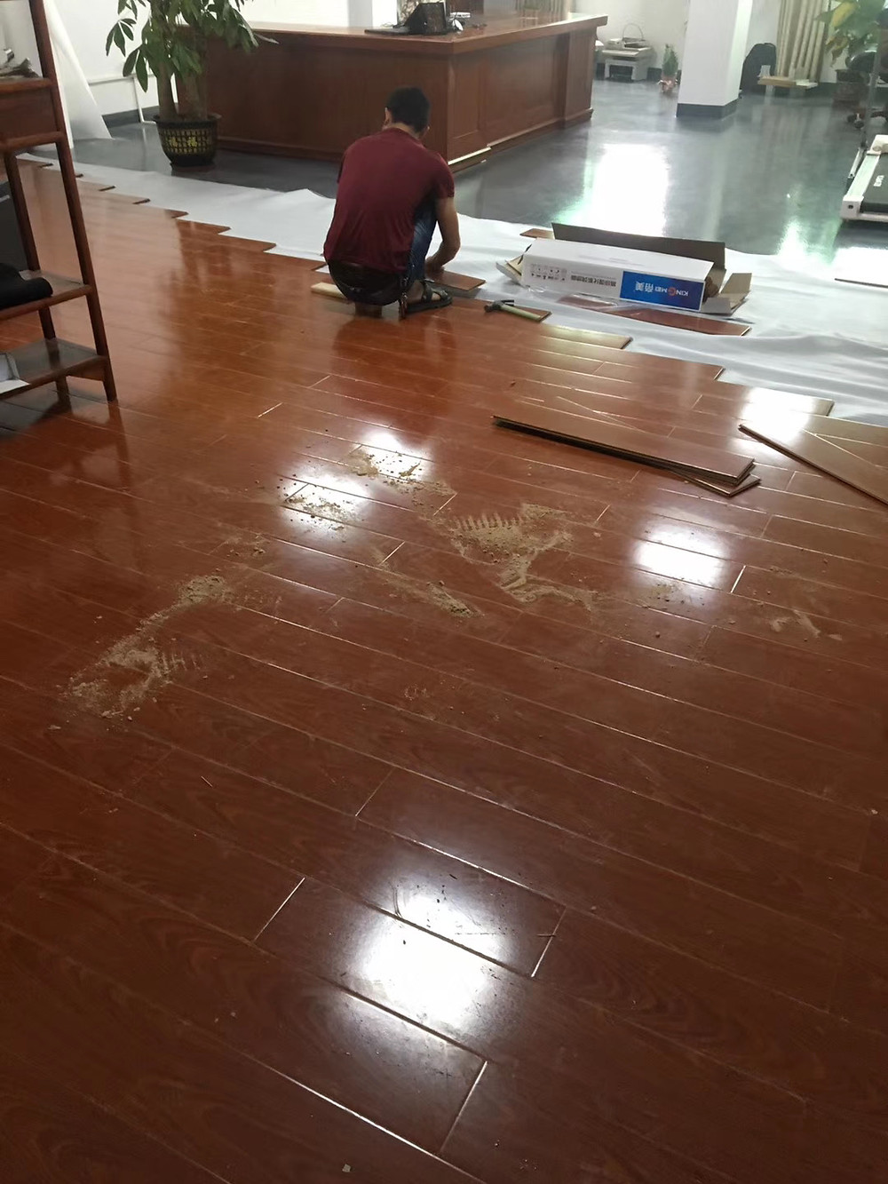 Our professional installers installing laminate wooden flooring for office.