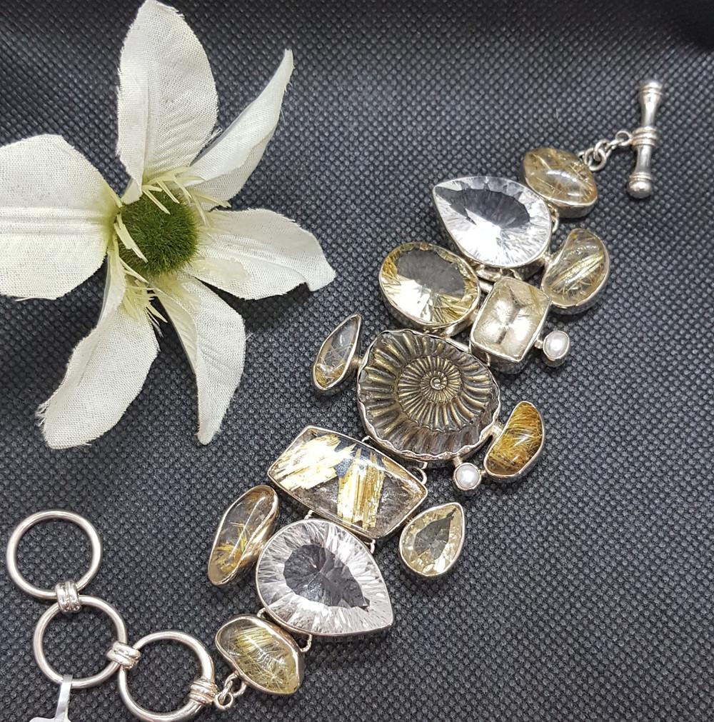 Silberarmband welches eine ganze Welt fantastischer Schmucksteine in sich vereint: mittig der Abdruck eines Ammoniten, drumherum drappiert Rutilquarze mit ihren goldfarbigen nadelförmigen Einlagerungen und leuchtend fascettierte weiße Topase